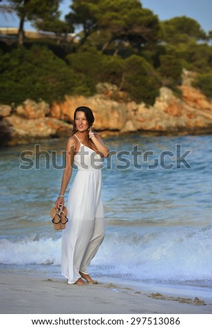 young attractive and beautiful woman enjoying vacation summer holidays at Spain coast village walking on beach sand letting white dress getting wet on sea water relaxed and happy