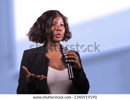 young attractive and confident black African American business woman with microphone speaking in auditorium at corporate event or seminar giving motivation and success coaching conference
