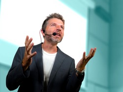 young attractive and confident successful man with headset speaking at corporate business coaching and training auditorium conference room talking giving motivation training from speaker stage