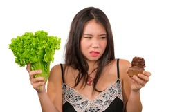 young attractive and confused Asian Korean woman holding delicious and tempting chocolate cupcake and healthy green lettuce struggling choice low calories versus unhealthy sugary cake