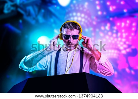 young attractive and cool DJ in shirt and suspenders remixing music at night club using headphones in party strobo and flash lights background in clubbing and nightlife concept