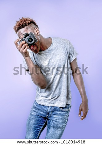 young attractive and cool happy black afro American man holding digital reflex photo camera smiling excited isolated background in photographer learning and practicing photography hobby