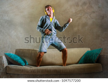 young attractive and cool happy man playing air guitar listening to music with yellow headphones holding mobile phone jumped on top of home sofa couch excited in trance isolated on grunge bg