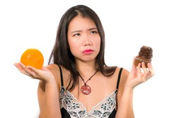 young attractive and happy Asian Chinese woman holding delicious and tempting chocolate cupcake full of calories and fresh healthy orange fruit in low calories versus sugary junk food