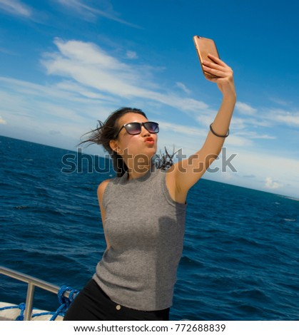young attractive and happy Asian Chinese woman selfie portrait picture with mobile phone on boat or ferry smiling with blue sea background in holiday ship trip excursion concept
