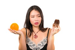 young attractive and happy Asian Japanese woman holding delicious and tempting chocolate cupcake full of calories and fresh healthy orange fruit in low calories versus sugary junk food