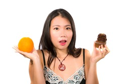 young attractive and happy Asian Korean woman holding delicious and tempting chocolate cupcake full of calories and fresh healthy orange fruit in low calories versus sugary junk food