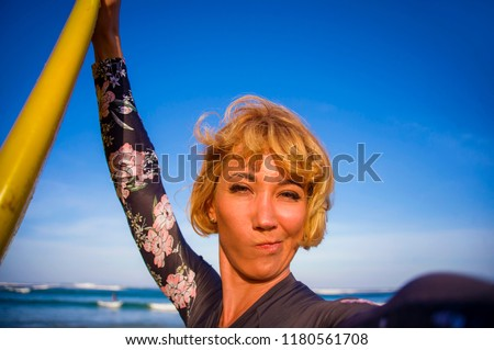 young attractive and happy blonde surfer woman in swimsuit holding surf board in the beach taking self portrait selfie picture smiling playful enjoying holidays at tropical island