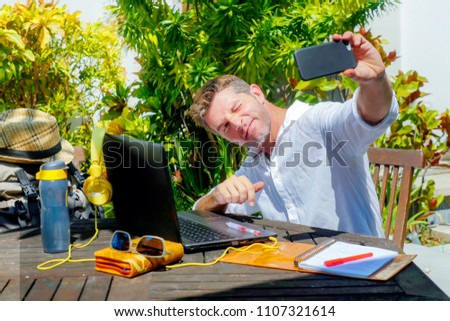 young attractive and happy digital nomad man working outdoors from coffee shop with laptop computer taking selfie pic relaxed and confident in traveler and business travel lifestyle concept