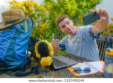 young attractive and happy digital nomad man working outdoors with laptop computer cheerful taking selfie pic with mobile phone in freelancer and independent job success concept