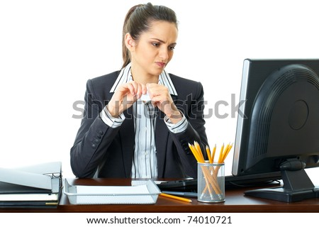 young attractive angry office worker, trying to tear some papers, isolated on white