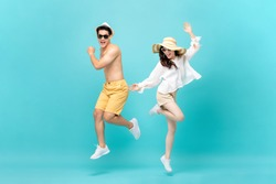 Young attractive Asian couple jumping together isolated on light blue studio background