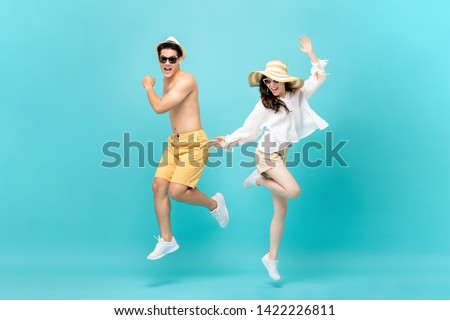 Young attractive Asian couple jumping together isolated on light blue studio background #1422226811