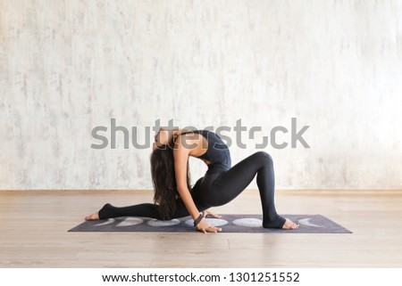 Young attractive asian dark skin woman practicing yoga, standing in anjaneyasana exercise, Horse rider pose, wearing black sportwear, indoor full length, home interior. Concept of healthy lifestyle #1301251552