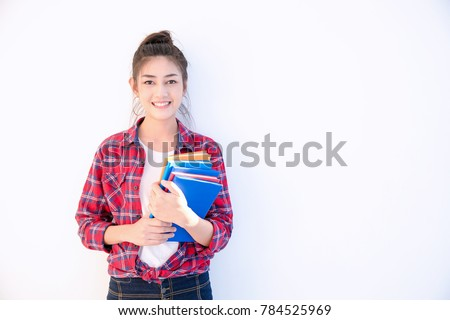 Young attractive asian student holding colorful books in her arm on white background. Smiling girl in colorful t-shirt hold many books. School girl with a lot books to read for homework.