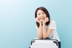 young attractive asian woman and suitcase