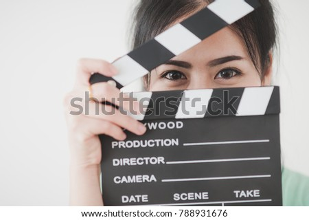 Young attractive Asian woman holding clapperboard with positive feeling. Film production and movie making concept #788931676