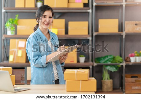 Young attractive asian woman owner startup business look at camera work happy with box at home prepare parcel delivery in sme supply chain, procurement, omnichannel or coronavirus quarantine concept. Stockfoto ©
