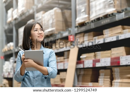 Young attractive asian worker, owner, entrepreneur woman holding smart tablet computer looking side up above shelf with efulfillment service business warehouse online concept. Asian sme merchandise.