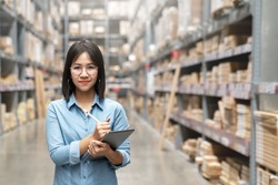 Young attractive asian worker, owner, entrepreneur woman holding smart tablet looking at camera with concept efulfillment service business warehouse management stock online. Asian sme merchandise.