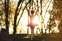 Young attractive ballerina silhouette garden training opposite sunrise or sunset. Fine art ballet concept. Teenager girl forest Surreal dancing. Concept of new life beginning. Active and healthy kid