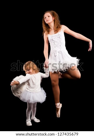 Young attractive ballerina with 2 years old angel. Isolated on black
