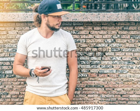 ad77e269840 Young attractive Bearded man wearing gray T-shirt mockup and Blank Blue Cap  holding modern