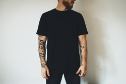 young attractive bearded man with tattoos, dressed in a black blank t-shirt, posing on a white wall background. Empty space for you logo or design.