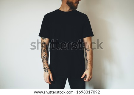 young attractive bearded man with tattoos, dressed in a black blank t-shirt, posing on a white wall background. Empty space for you logo or design. Stock fotó ©