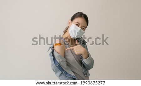 Young attractive beautiful asia female or teenage receive covid-19 anti virus vaccine in campaign vaccination safe life happy smile cheerful with blue, yellow, pink bandage on arm with copy space.