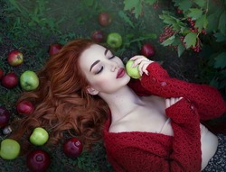 Young attractive beautiful red-haired woman with green and red apples and Rowan berries in a fairy light. Art processing. Autumn colors.