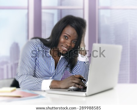 young attractive black African American ethnicity woman working at computer laptop at business district office desk smiling happy in success career concept in pink tinted background