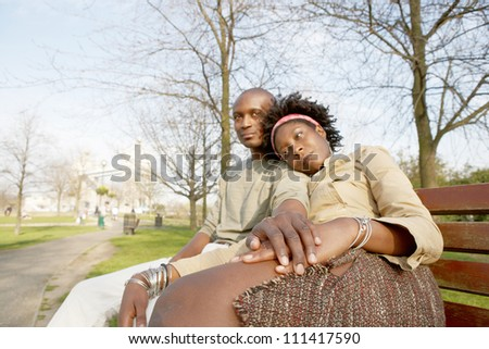 Young attractive black couple sitting down on a bench in the park while visiting the Tower of London, holding hands.