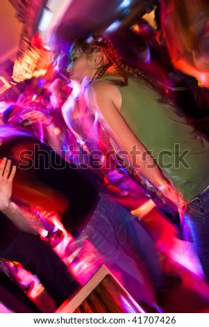 Young attractive blond girl on the crowded dancefloor - stock photo