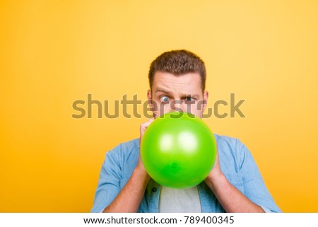 Young attractive blond man tired to blow up balloons new year party, twisted eyes over yellow background Foto stock ©