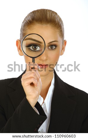 Young attractive blonde business girl holding magnifying glass in front of her eye
