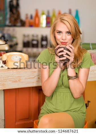 young attractive blonde girl sitting on a chair near the conter of a colorful cafe with a coffee mug in her hands