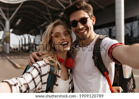 Young attractive blonde woman in plaid shirt and stylish brunette man in sunglasses smiles and takes selfie. Portrait of couple of travelers near airport. Foto stock ©