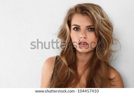 Young attractive blonde woman looking at camera studio portrait