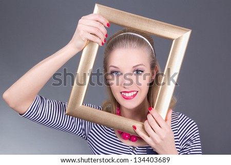 young attractive blondie pinup girl in striped dress with photo frame over grey
