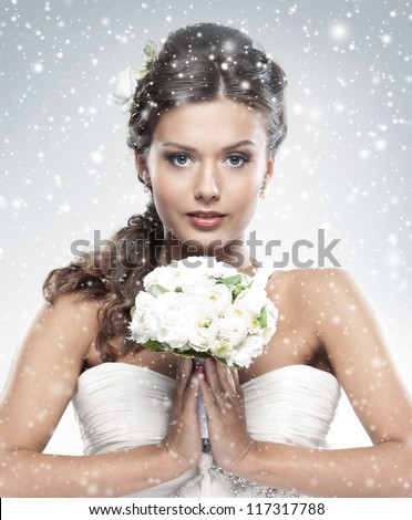 Young attractive bride with the bouquet of white roses over snowy Christmas background