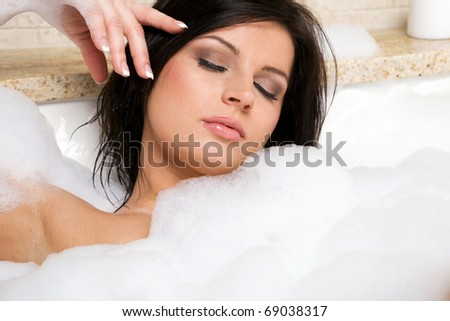 Young attractive brunette relax taking a bath. - stock photo