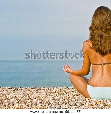 Young attractive brunette woman in swim suit doing yoga moves or meditating on sea beach