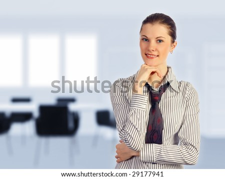 Young attractive business woman in a meeting room (blurred background).