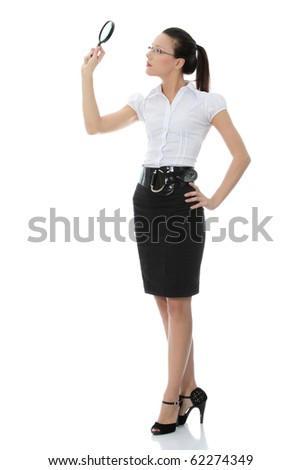 Young attractive business woman looking into a magnifying glass, isolated on white background