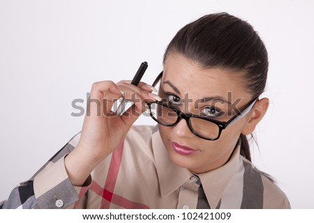 Young attractive business woman looking through her glasses.