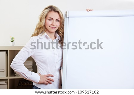 Young attractive business woman standing in her office with a flipchart