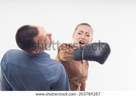 Young attractive business woman with boxing gloves striking man standing from behind, isolated on white background