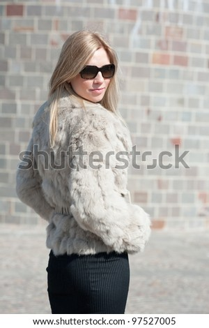 Young attractive business woman with fur in front of modern business offices center.