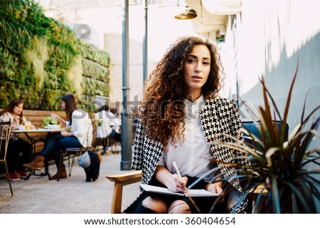 Young attractive business woman with long curly hair holds a job interview in a coffee-shop.beautiful girl takes a journalist interviews